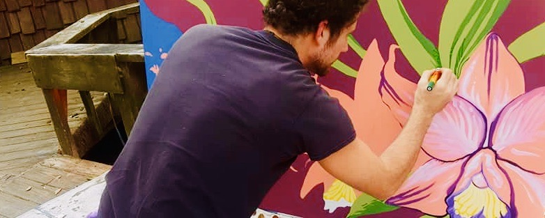 Ian Cleary paints an Orchid  mural at The Hostel in the Forest