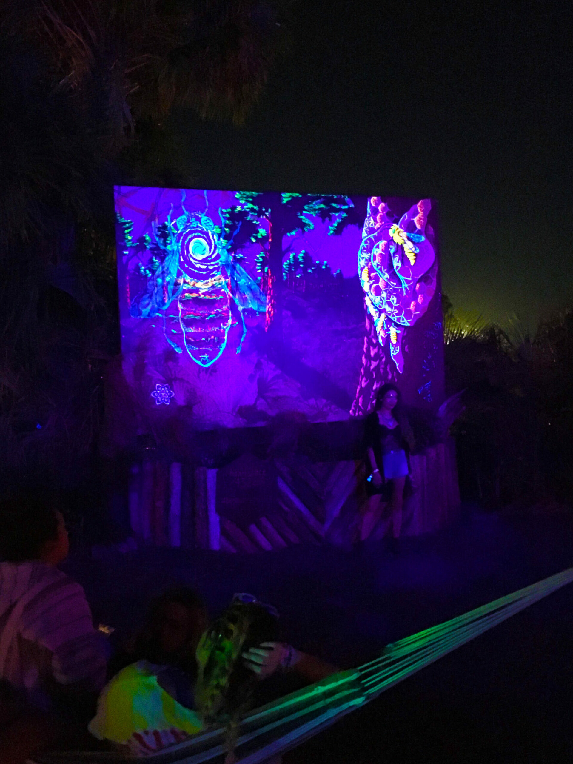 This image is the Bee Aware mural under UV lights. The lights reveal elements hidden in the painting under normal lighting. This Mural was installed at the Okeechobee music festival.