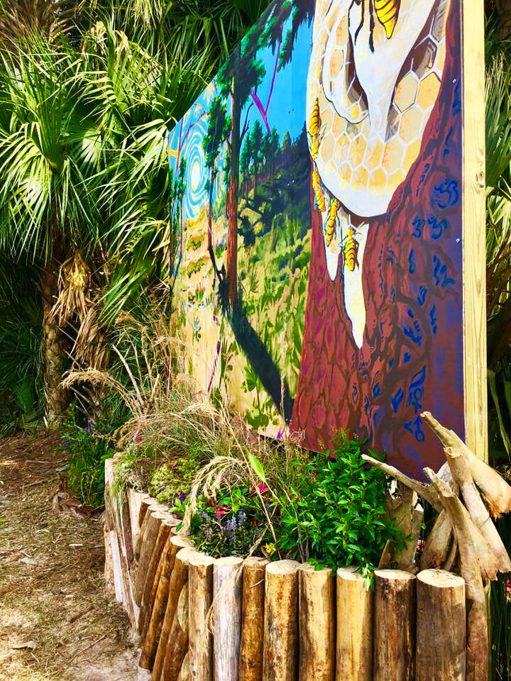 This image is the Bee Aware mural and displays the native plant garden. The native plant garden was designed to enhance the beauty of the space and bring in local pollinators. This Mural was installed at the Okeechobee music festival.