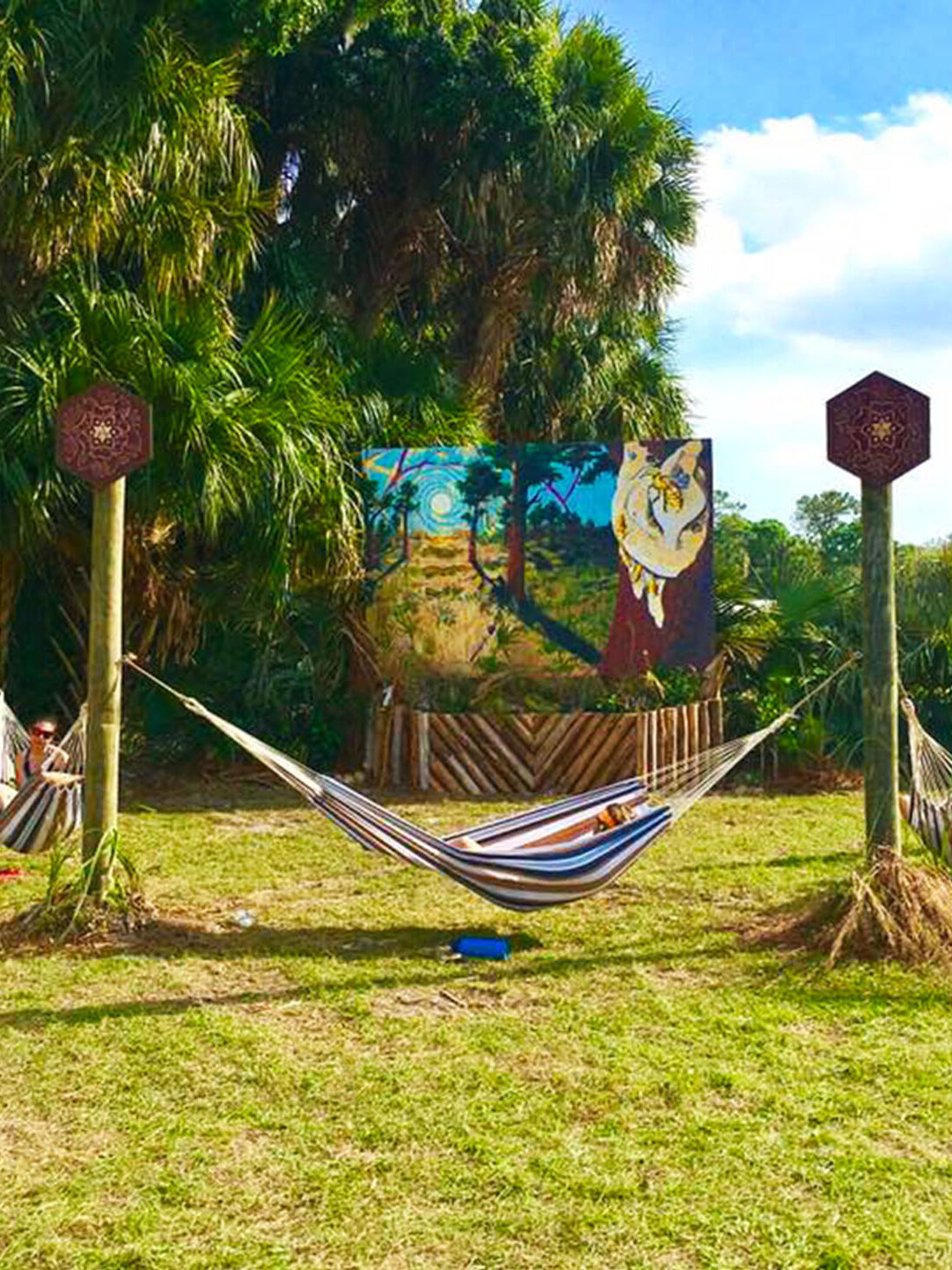 Bee Aware mural at the Okeechobee Music Festival. Created by heartspace art, this mural has a message about the importance of bees in our ecosystem. This photo shows the entire installation including the hammock hang out.