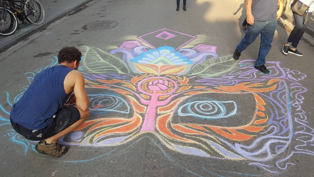 Ian Cleary working on Heartspace Art chalk art mural, entitled Feminine Mystique, created in New Orleans for the Women's March.